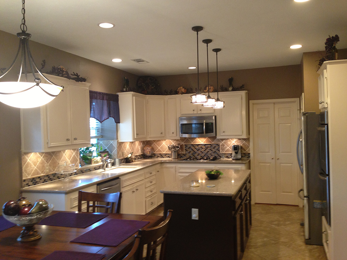 A kitchen with remodelled cabinets, countertops, custom lighting and more