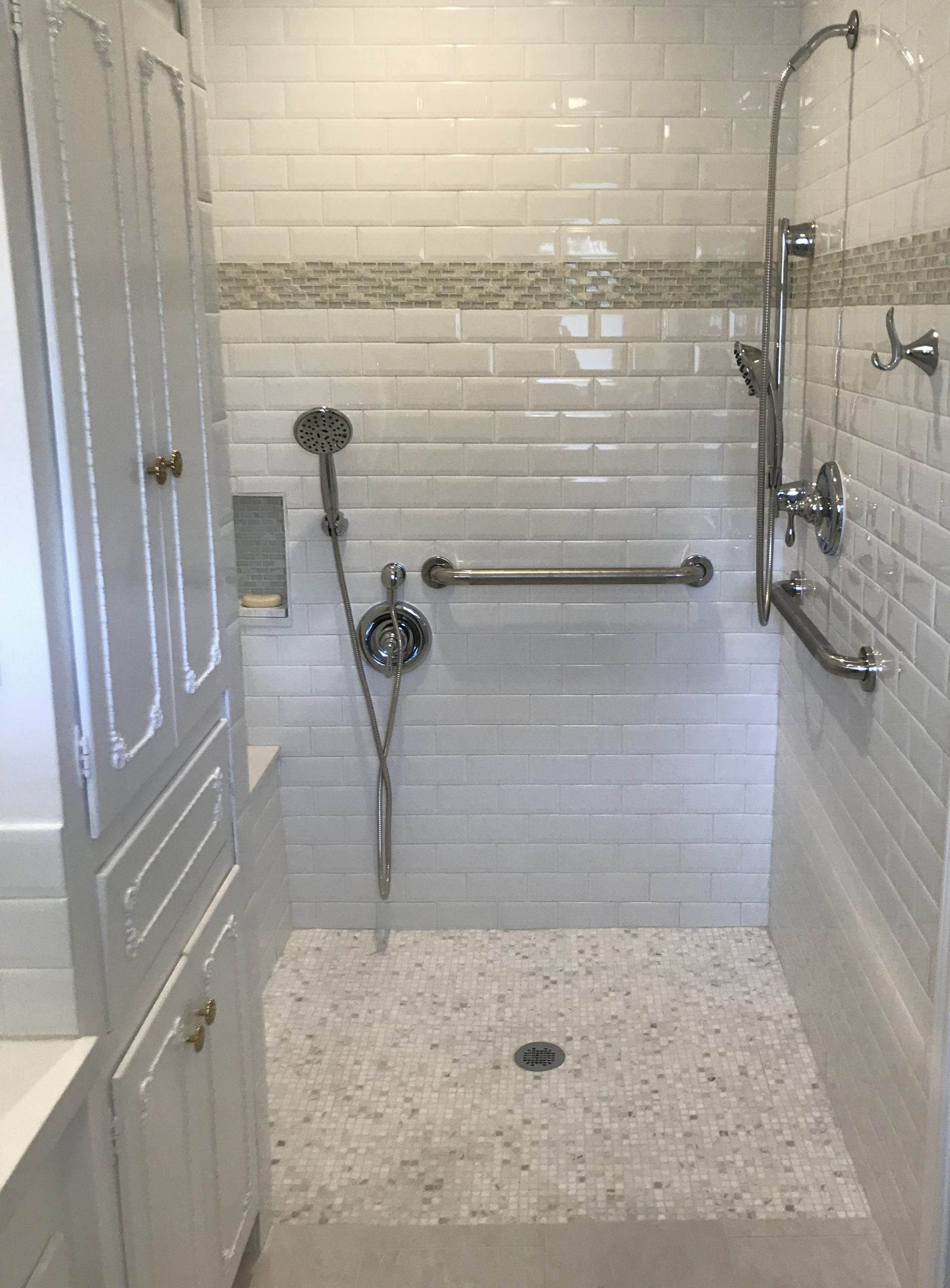 A remodeled ADA compliant bathroom with custom cabinets, floors, multiple shower heads and plumbing